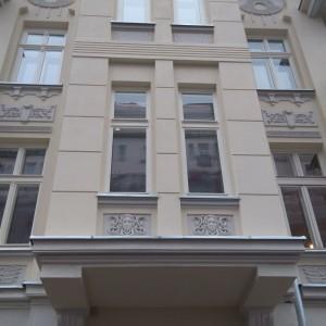 Elewacja zewnętrzna budynku z oknami zdobieniami w kształcie głów