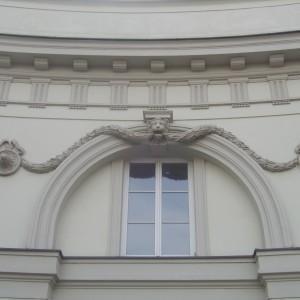 Detal w kształcie lwa z liną w pysku nad oknem